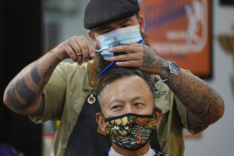 In this May 27, 2020 file photo Luis Lopez wears a face mask while giving a h...
