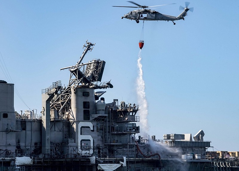 An Sea Hawk helicopter provides aerial firefighting support to fight the fire...