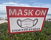 A sign warning people to wear masks due to COVI...