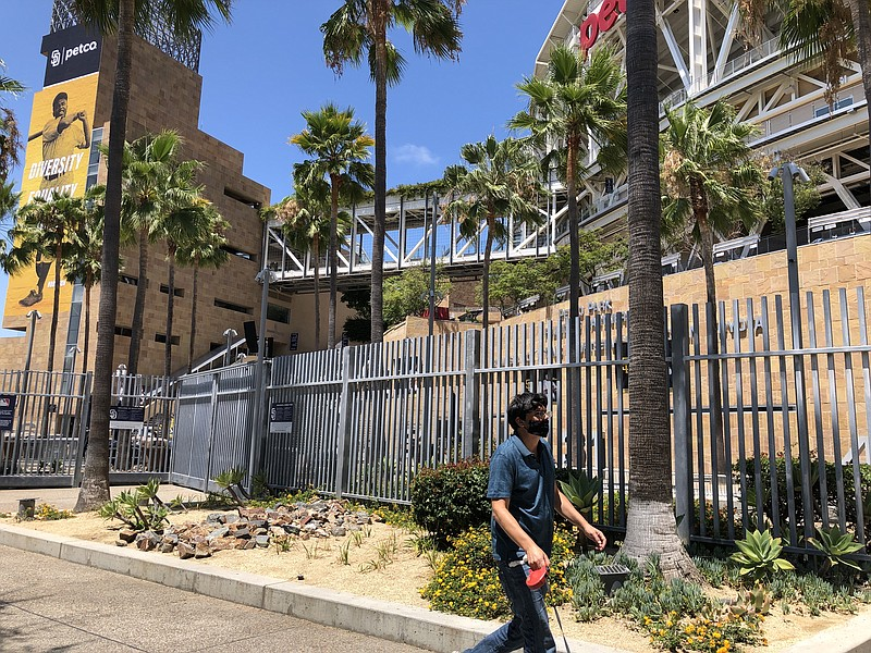 A pedestrian in a mask walks by Petco Park in Downtown San Diego. July 24, 20...