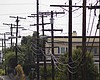 A trail of electric grid wires and poles travel...