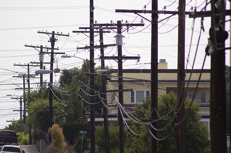 A trail of electric grid wires and poles travels across the skyline in South ...