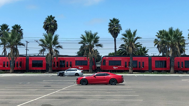 Two cars are seen parked at the Palm Avenue trolley station as a trolley pass...