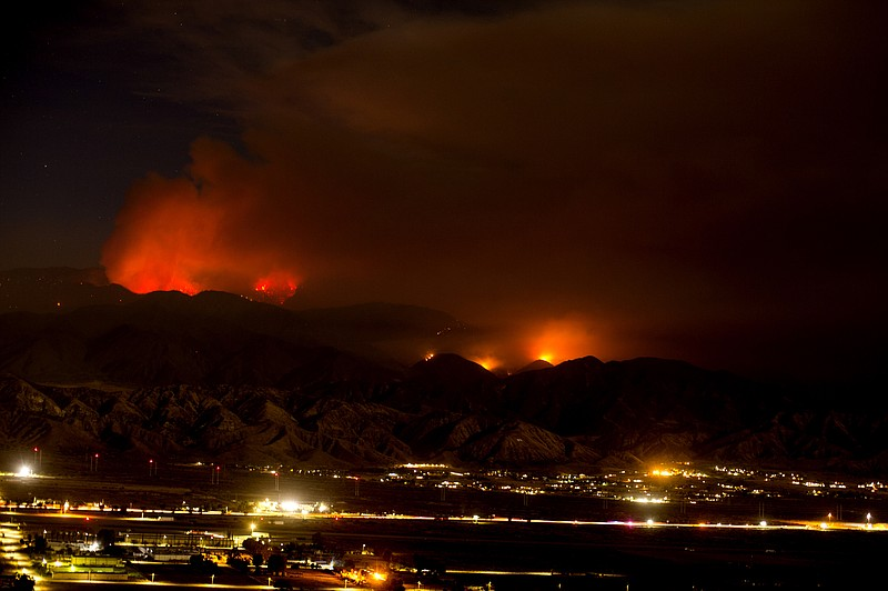 The Apple Fire burns behind mountains near Beaumont, Calif., Sunday, Aug. 2, ...