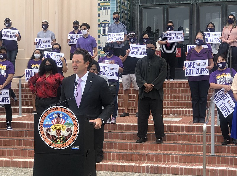 Sign-carrying union members stand behind San Diego County Supervisor Nathan F...