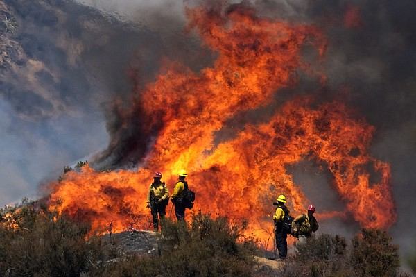 Firefighters watch the Apple Fire in Banning, Calif., Sun...