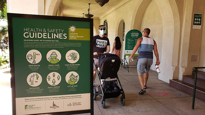 A man with a stroller on Aug. 1, 2020, walks by a Balboa Park health and safe...
