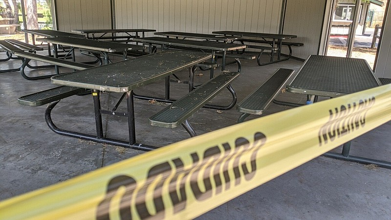 Picnic tables are seen behind yellow caution tape in the pavilion at Sweetwat...