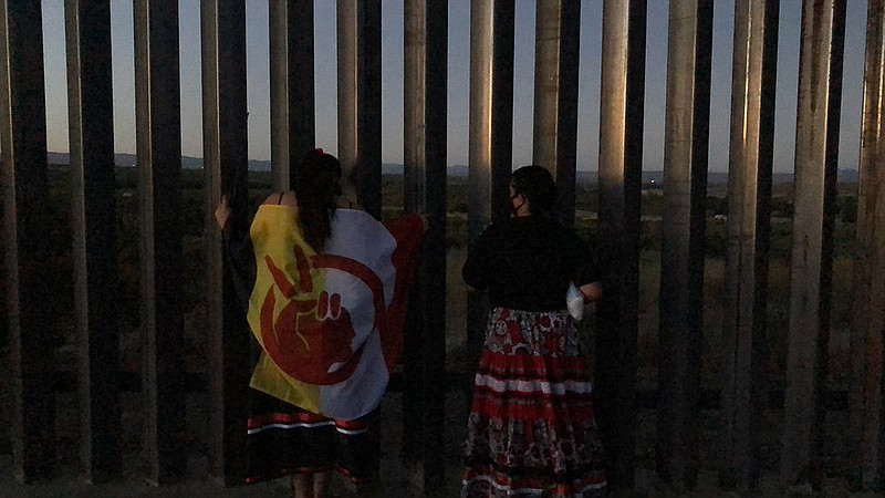 Kumeyaay protesters stand next to newly-built border wall in the Laguna Mount...