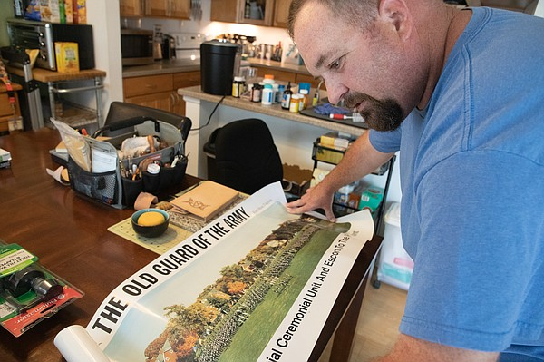 Army veteran Joel Andrews shows a photo from when he was ...
