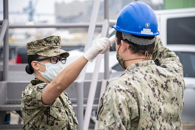 Sailor receives a temperature check before boarding the USS Bonhomme Richard,...