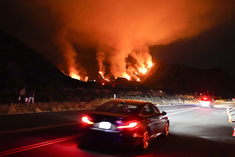 Motorists make their way along a road as the Ranch Fire burns, Thursday, Aug....