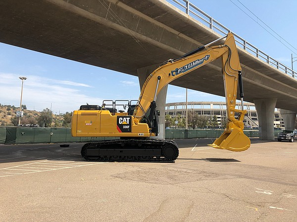 A hydraulic excavator moves out from under the railway ov...