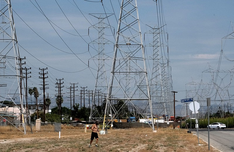 A jogger runs in extreme heat under high tension electrical lines in the Nort...