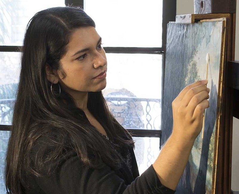 Art conservator Bianca Garcia cleans a painting. This month, the Balboa Art C...