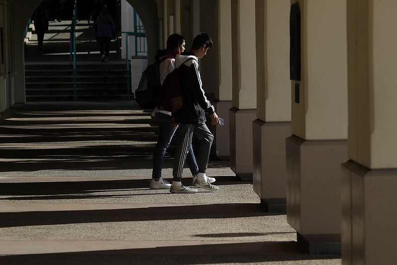 Students walk on the San Diego State University campus Thursday, March 12, 20...