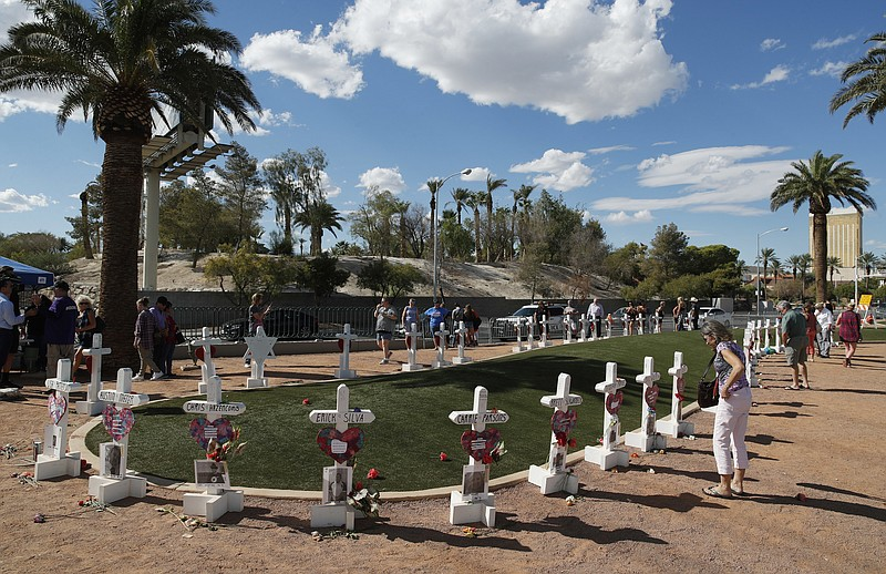 In this Sept. 30, 2018, file photo, people visit a makeshift memorial for vic...