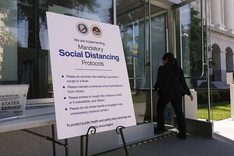 A sign outside the California state capitol advising people of social distanc...