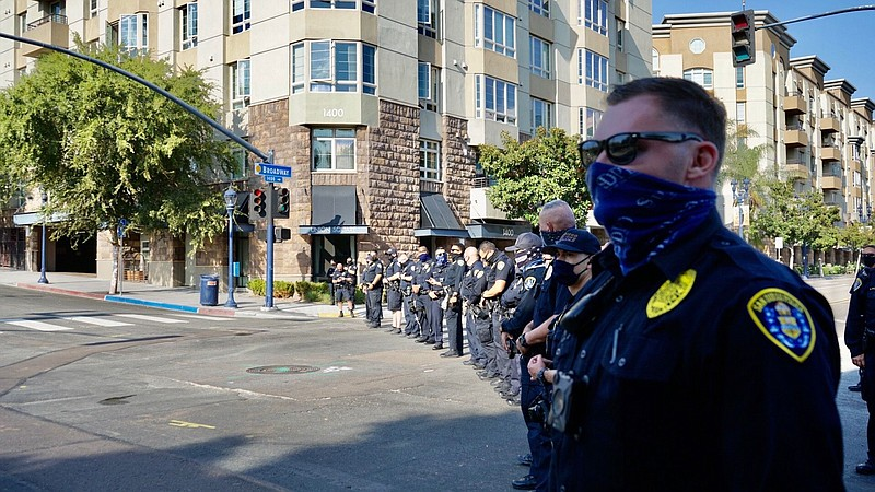 A line of police officers in front of the San Diego Police Department headqua...