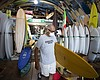 Surf shop worker Scat wears a mask while carryi...