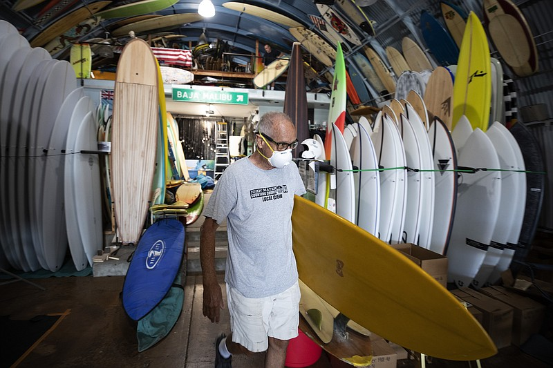 Surf shop worker Scat wears a mask while carrying a surfboard at Bird's Surf ...