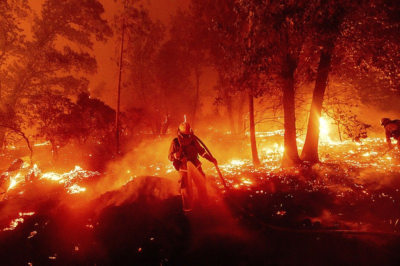 A firefighter battles the Creek Fire as it threatens homes in the Cascadel Wo...