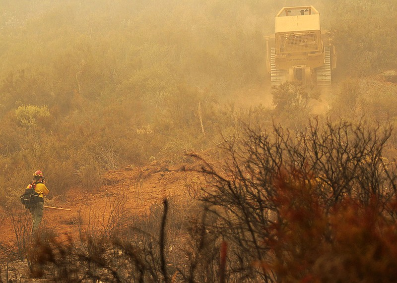 A Cal Fire firefighter talks on a radio during efforts to extinguish the Vall...