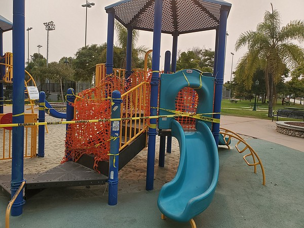 A City Heights playground wrapped in orange fence and cau...