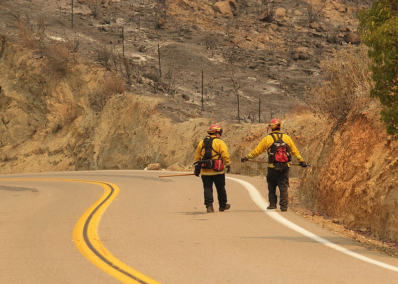 Two Cal Fire firefighters walk down a road during efforts to fight the Valley...