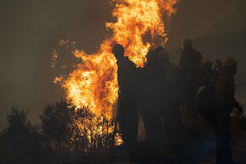 Firefighters monitor a controlled burn along Nacimiento-Fergusson Road to hel...
