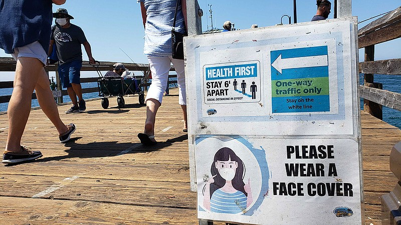 A sign warns people to practice social distancing and to wear a mask at the I...