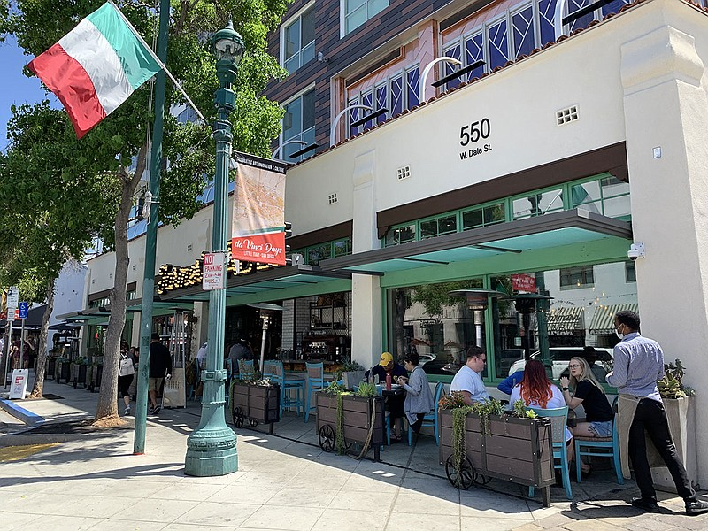 Customers sit in an outdoor dining area on India Street in Little Italy, June...