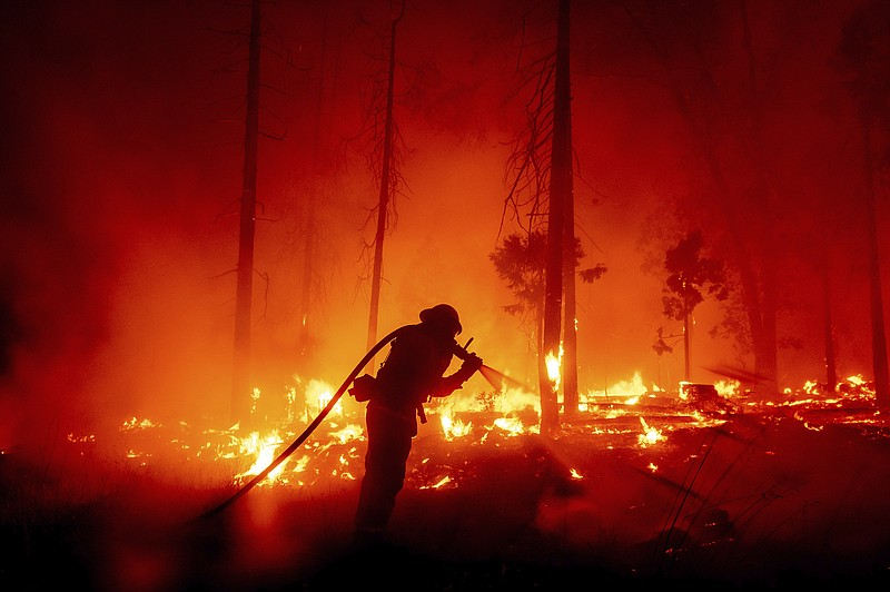 In this Sept. 7, 2020, file photo, a firefighter battles the Creek Fire as it...