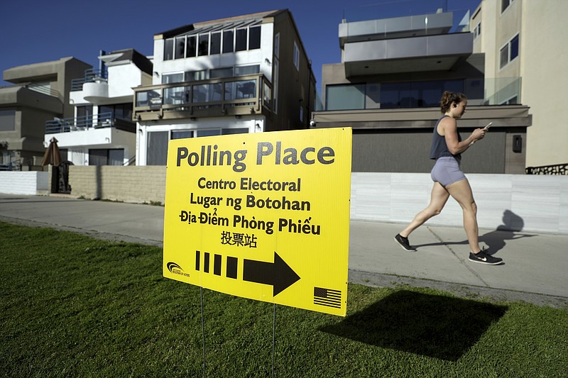 In this March 3, 2020 file photo, a woman runs on a path by a polling place d...