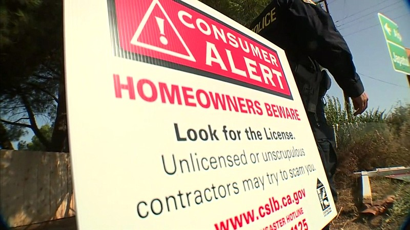 A sign to ward off scammers and unlicensed contractors is placed by police in...