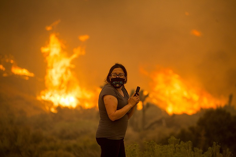A woman watches as the Bobcat Fire burns in Juniper Hill, Calif., Friday, Sep...