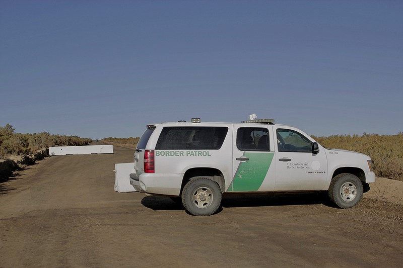 A Border Patrol vehicle blocks a road leading to the construction site for th...