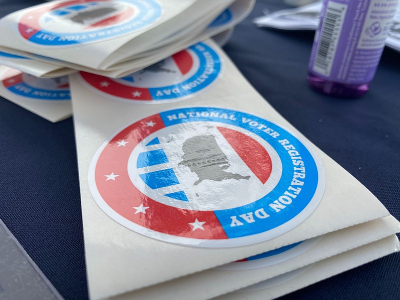 A sticker for National Voter Registration Day sits on top of a League of Wome...