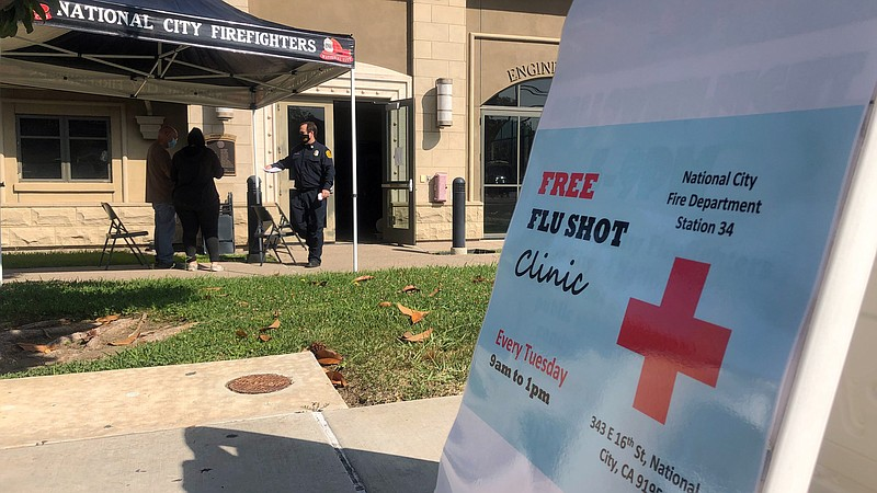 A National City paramedic greets people waiting for free flu shots outside Fi...
