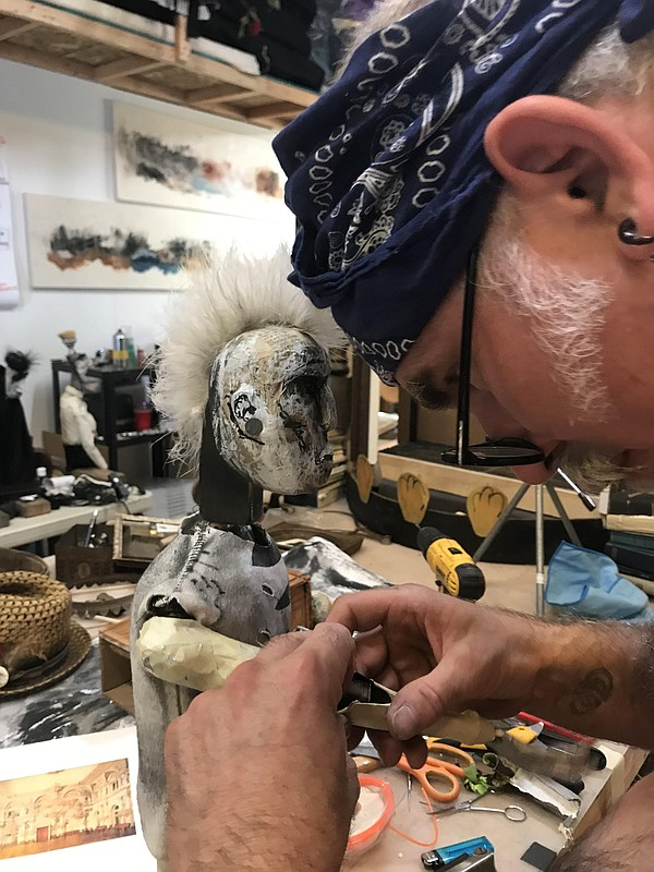 Iain Gunn works on one of the puppets from