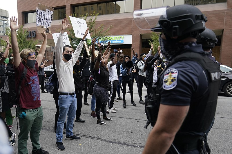 Protesters chant near police, Wednesday, Sept. 23, 2020, in Louisville, Ky. A...