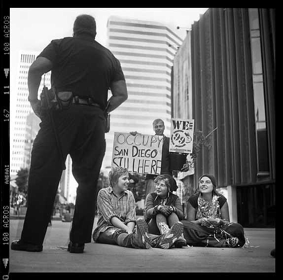 A police officer stands near protesters during the 2011 O...