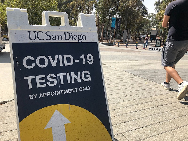 A man walks by a COVID-19 testing sign at UC San Diego campus, Sept. 28, 2020.