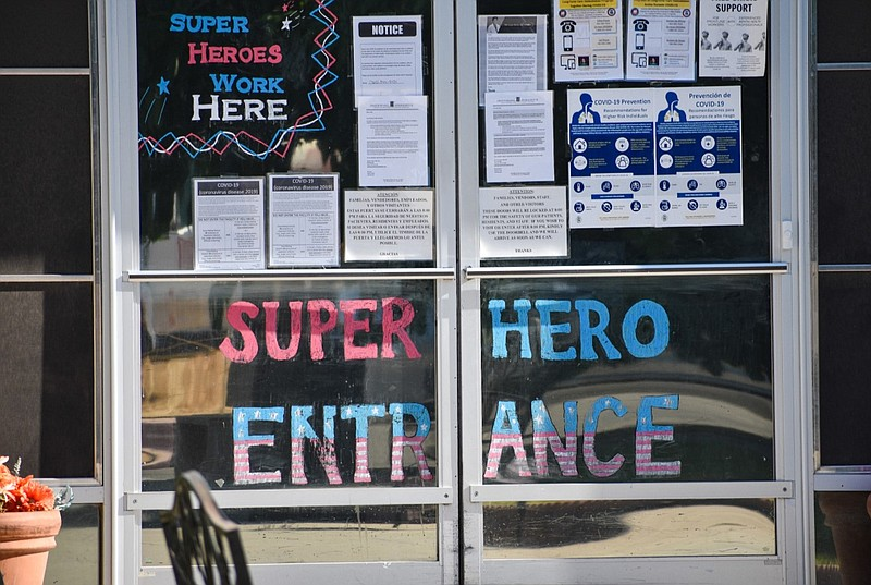 The signs on a door at the Imperial Heights nursing home in Brawley is shown ...