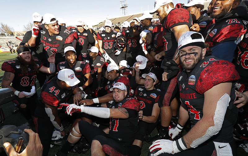 San Diego State football players celebrate after they beat Central Michigan i...