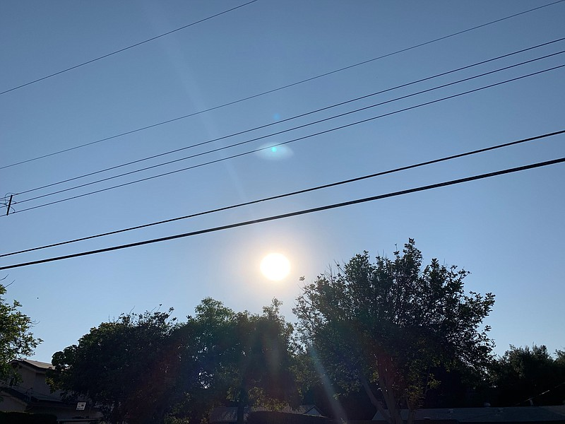 The sun rises above power lines in the San Carlos neighborhood in San Diego, ...