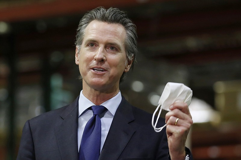 In this June 26, 2020 file photo, Gov. Gavin Newsom holds a face mask as he u...
