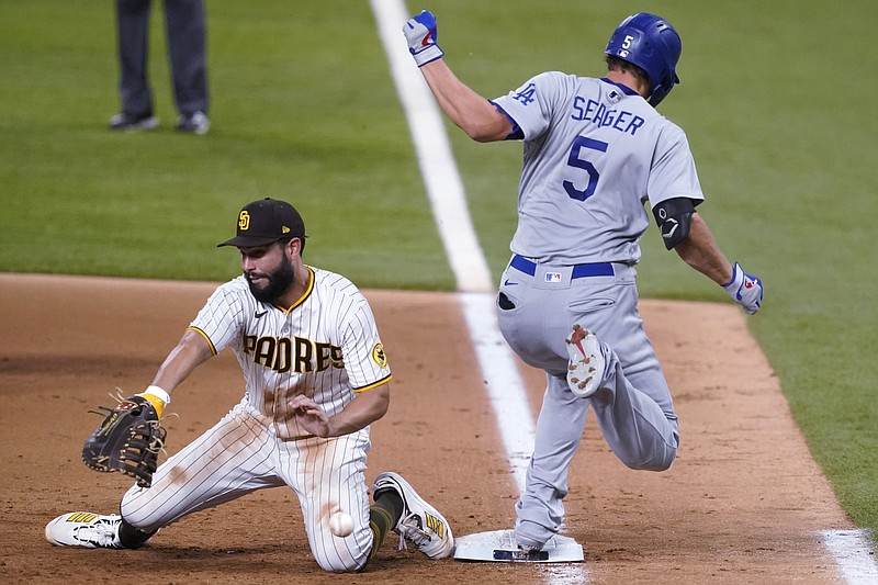 San Diego Padres' Eric Hosmer, left, tries to control the ball as Los Angeles...