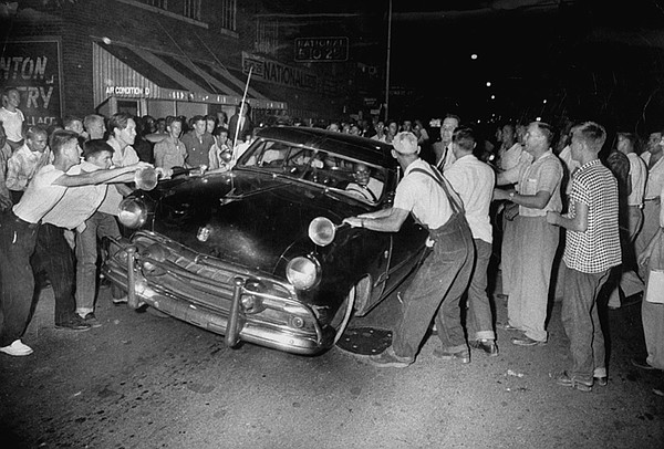 A crowd attacking cars driven by African Americans to pro...
