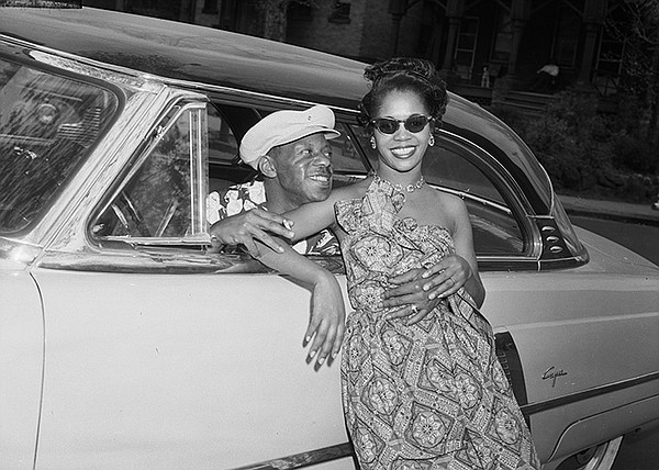 Woman posed against 1952 Lincoln Capri coupe car, with ma...